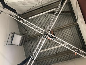 Evgeny Greshilov crouched on top of an aerial truss filming the aradia fitness calgary feature video