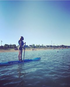 Aradia Fitness Calgary Student Victoria on a paddle board wearing a life jacket.