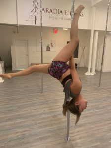Student spotlight Victoria showing off an outside ankle hook on the pole