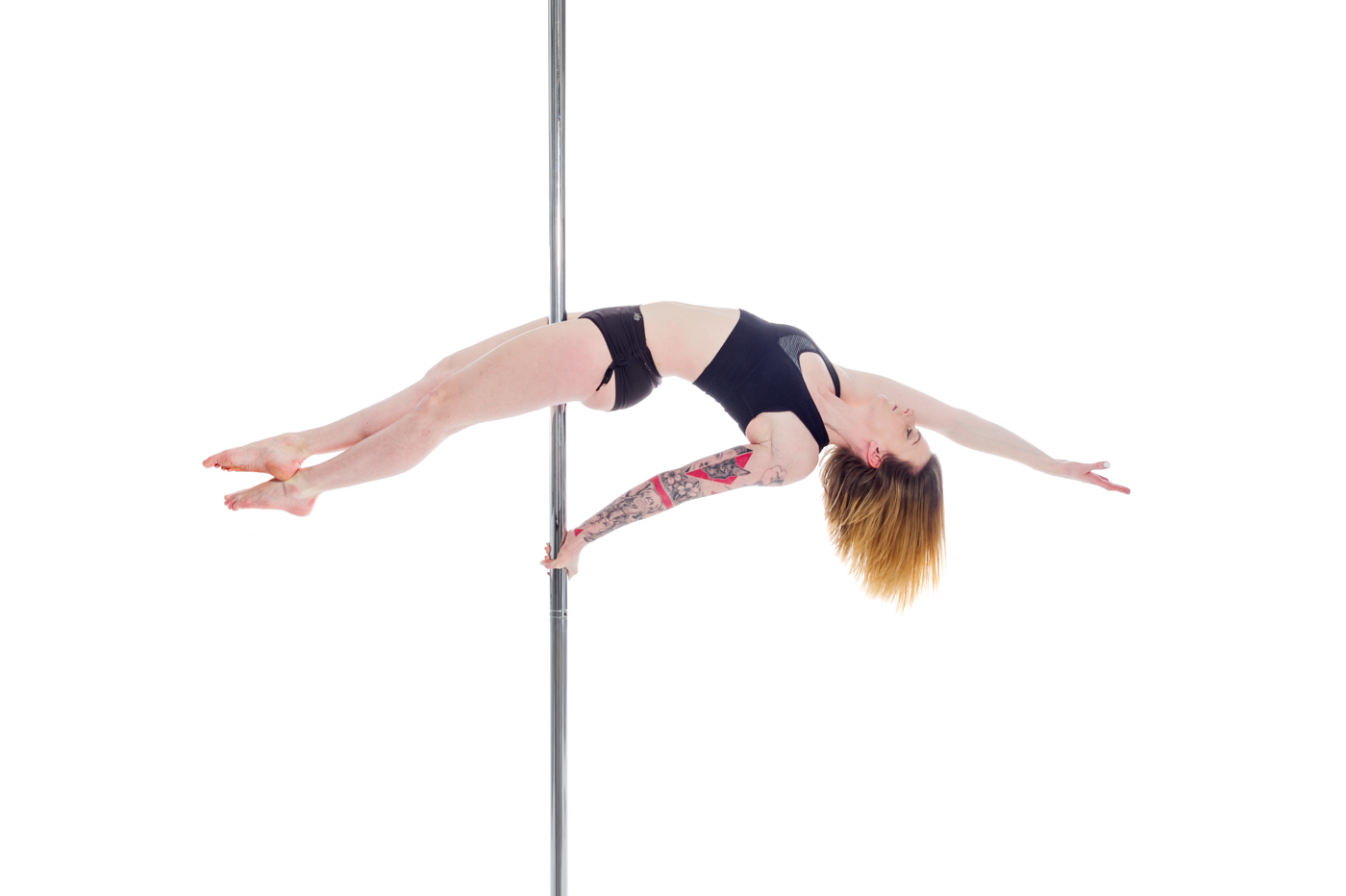 Aradia Fitness Calgary instructor Angela showing off a table move on pole