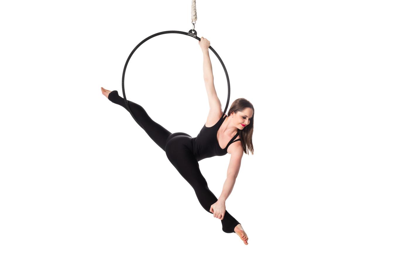 Woman in black leotard in split pose on lyra