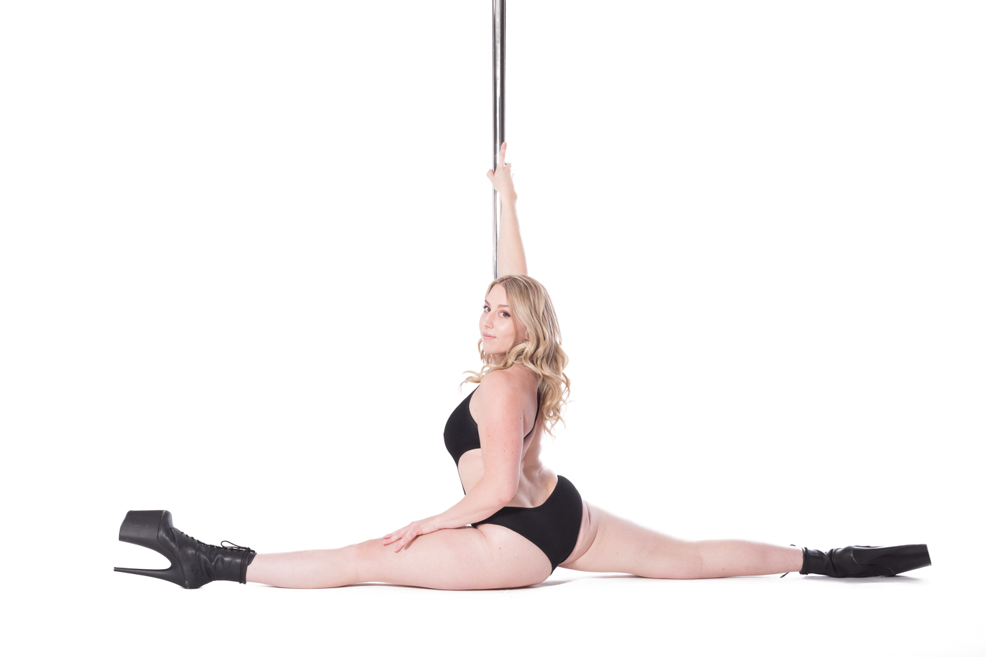 Featured Aradia Fitness Calgary instructor Jordanna in a floor split with pole