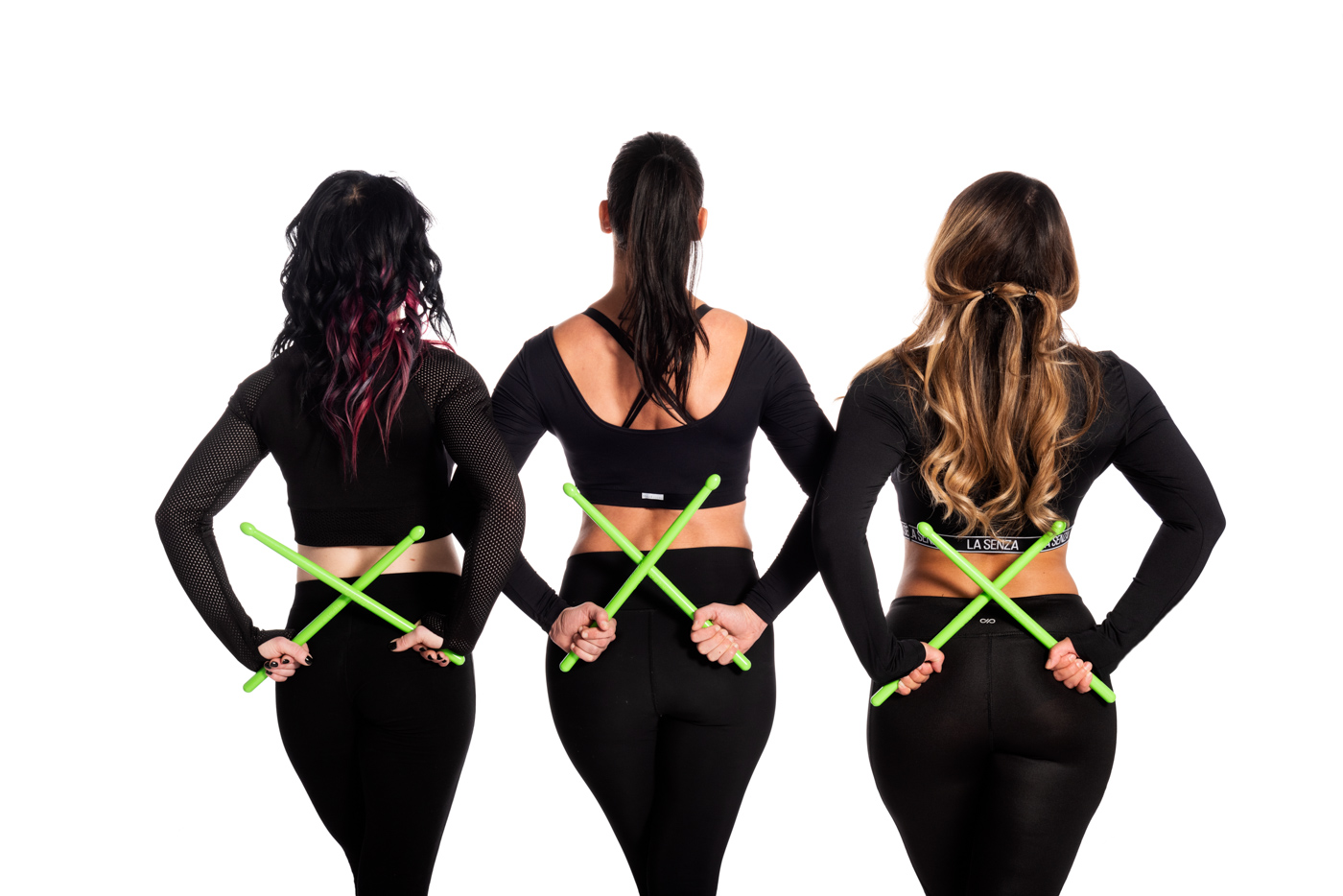 Three POUNDfit trainers standing with ripstix crossed behind their backs